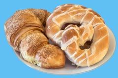 Pasta e ciambellina salata sfoglia fresca del croissant del sesamo servite sul piatto bianco isolato su fondo blu Fotografie Stock Libere da Diritti