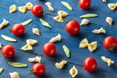 Pasta e pomodori ciliegia a forma di crudi immagine stock