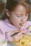 Pasta eating. A girl eating Italian pasta\tagliatelles with a ham of Parma and mushrooms Royalty Free Stock Photography