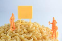 Pasta ed insieme crudi degli operai su un fondo bianco Fotografie Stock Libere da Diritti