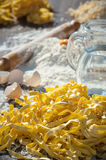 Pasta egg in flour and a rolling piñon wood and rustic table. Stock Photos