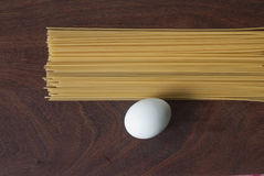 Pasta and egg. On a wooden background Royalty Free Stock Photos