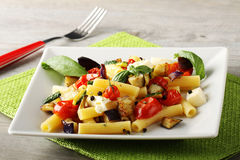 Pasta with eggplant, cherry tomatoes and mozzarella. On complex background Stock Images