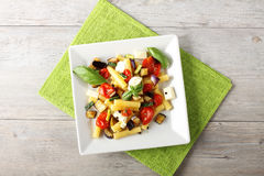 Pasta with eggplant, cherry tomatoes and mozzarella. On complex background Royalty Free Stock Photography