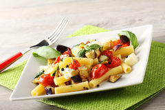 Pasta with eggplant, cherry tomatoes and mozzarella. On complex background Stock Photo