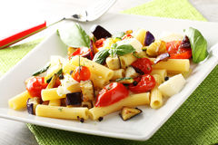Pasta with eggplant, cherry tomatoes and mozzarella. On complex background Royalty Free Stock Photo