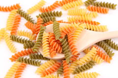 A pasta eliche tricolori and a wood spoon. Royalty Free Stock Photography