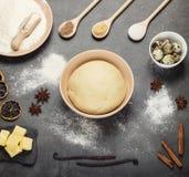 Pasta en cuenco, mantequilla en la placa de la pizarra, harina, huevos y especias, en superficie gris imagenes de archivo