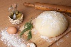 Pasta en un tablero con la harina aceite de oliva, huevos, rodillo, garli Fotos de archivo libres de regalías