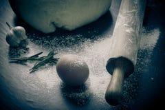 Pasta en un tablero negro con la harina huevos, rodillo, ajo Ti Foto de archivo
