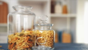 Pasta fall into a glass jar on white background stock video footage