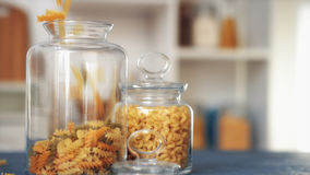 Pasta fall into a glass jar on white background Stock Image