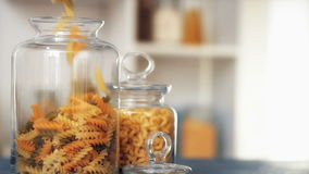 Pasta fall into a glass jar on white background stock footage