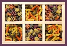 Pasta and farfalle. Some kinds of pasta and farfalle in wooden tray royalty free stock image