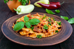 Pasta farfalle with chicken, tomato sauce and basil in a clay bowl Stock Photos
