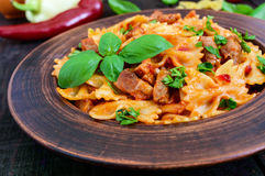 Pasta farfalle with chicken, tomato sauce and basil in a clay bowl on dark wooden background. Stock Photos