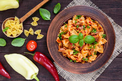Pasta farfalle with chicken, tomato sauce and basil in a clay bowl on dark wooden background. Royalty Free Stock Photo