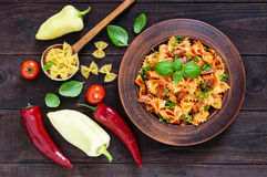 Pasta farfalle with chicken, tomato sauce and basil in a clay bowl on dark wooden background Royalty Free Stock Images