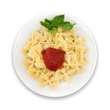 Pasta Farfalle med tomaten på plattan Isolerat på vit backgroun Arkivbilder