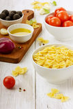 Pasta farfalle before preparation. On a wooden background Stock Images