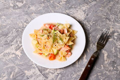 Pasta farfalle with salmon, zucchini and tomate Stock Photo