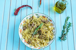 Pasta farfalle with turkey, pesto sauce and rosemary in serving plate over wooden turquoise background Stock Photography