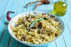 Pasta farfalle with turkey, pesto sauce and rosemary in serving plate over wooden turquoise background Royalty Free Stock Image