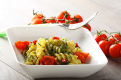 Pasta with fennel pesto, almonds and cherry tomatoes. On complex background Royalty Free Stock Photos