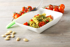 Pasta with fennel pesto, almonds and cherry tomatoes. On complex background Royalty Free Stock Images