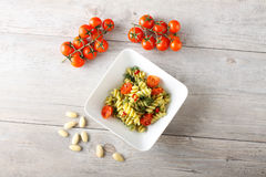 Pasta with fennel pesto, almonds and cherry tomatoes. On complex background Stock Images