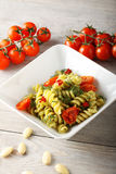 Pasta with fennel pesto, almonds and cherry tomatoes. On complex background Stock Image