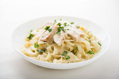Pasta fettuccine alfredo with chicken, parmesan and parsley on white background close up. Italian cuisine stock photos