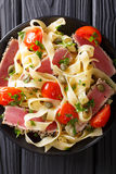 Pasta fettuccine with tuna steak, tomatoes and capers macro. Top. Pasta fettuccine with tuna steak, tomatoes and capers macro in a plate. Top view from above Stock Images