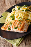 Pasta fetuccini with cheddar and grilled salmon on a plate close. Pasta fetuccini with cheddar cheese and grilled salmon on a plate close-up. Vertical Stock Image