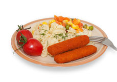 Pasta, fish sticks, cherry tomatoes and greens on plate with for Royalty Free Stock Photos