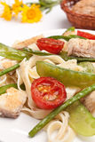 Pasta with fish and vegetables. Pasta with fish, tomatoes, asparagus and peas royalty free stock photography