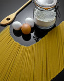 Pasta, flour container, eggs and spoon  Royalty Free Stock Photography