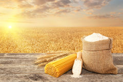 Pasta and flour on table. Uncooked pasta from durum wheat, wholegrain flour in bag and scoop on table with ripe cereal field on the background. Golden wheat royalty free stock images
