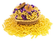 Pasta and flowers. Yellow pasta and flowers in the basket stock image