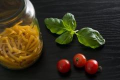 Pasta, foglie del basilico e pomodori ciliegia Fotografie Stock
