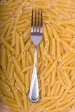 Pasta fork. Raw pasta background with a dinner fork on top stock photos