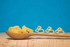 Pasta in the form of animals and a spoon on a blue background Royalty Free Stock Images