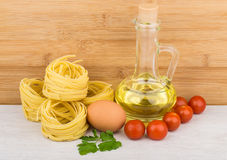 Pasta in form nest, bottle of oil, egg and tomatoes Royalty Free Stock Photography