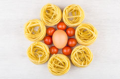 Pasta in form nest, egg and tomatoes cherry on table Royalty Free Stock Image
