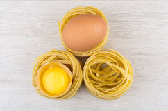 Pasta in form nest, egg and yolk in egg shell Royalty Free Stock Photography