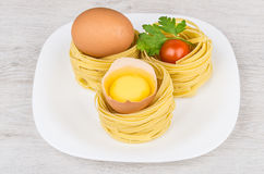 Pasta in form nest, egg and yolk in egg shell Royalty Free Stock Photo