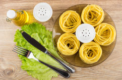 Pasta in form of nest in plate, bottle of oil Stock Photography