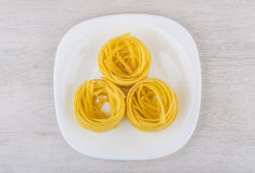 Pasta in form nest in plate on table Stock Images