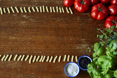 Pasta forming a frame with tomatoes and herbs Royalty Free Stock Photography