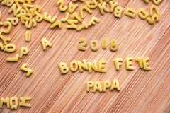 Pasta forming the text 2018 Bonne Fete Papa meaning Happy Fathers Day in French royalty free stock images
